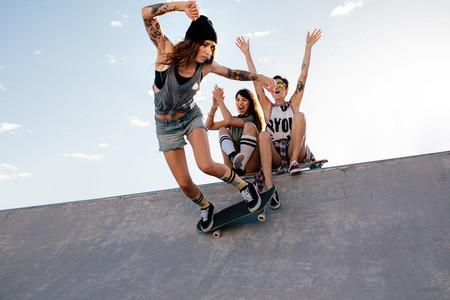 Skater girl rides on skateboard at skate park