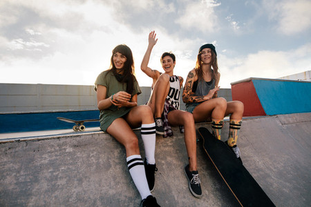 Group of female friends relaxing at skate park