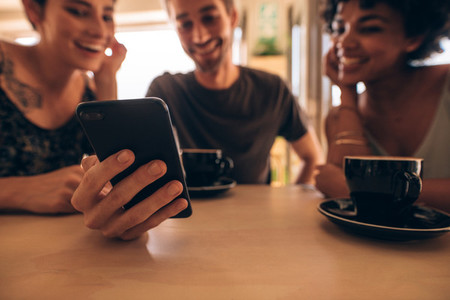 Man sharing pictures with friends at cafe