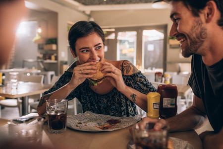Woman eating burger with friends at restaurant