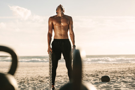 Man working out at the beach using battling rope and kettlebells