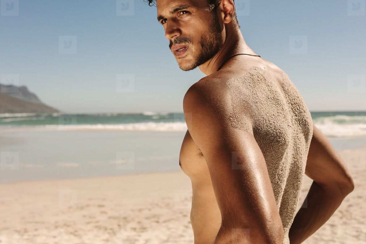 Man standing at the beach doing fitness training
