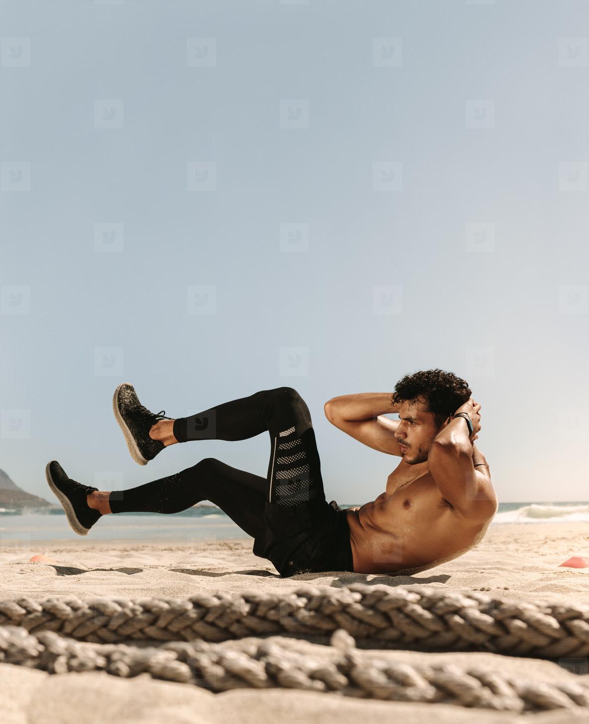 Man doing abdomen workout at the beach