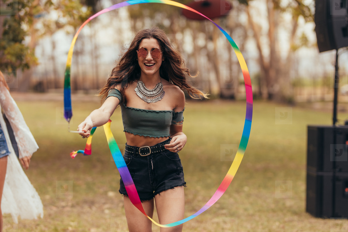 Woman playing with ribbon stick at music festival