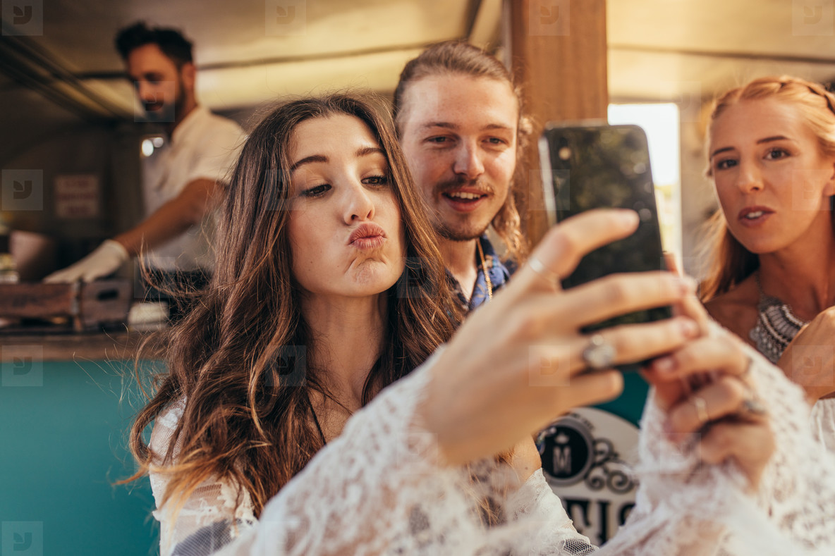 Beautiful woman taking selfie with friends