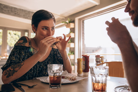 Woman having burger with boyfriend at restaurant