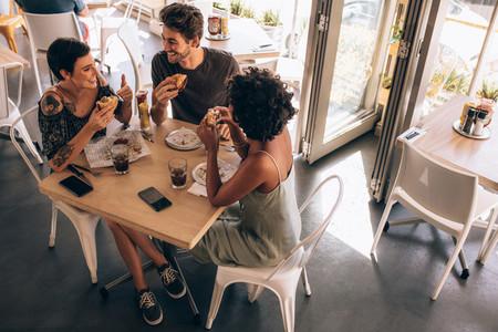 Friends having burger at restaurant