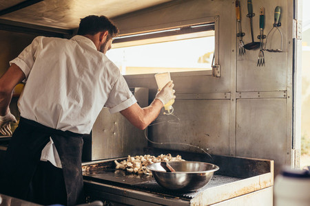 Male cook preparing food on truck