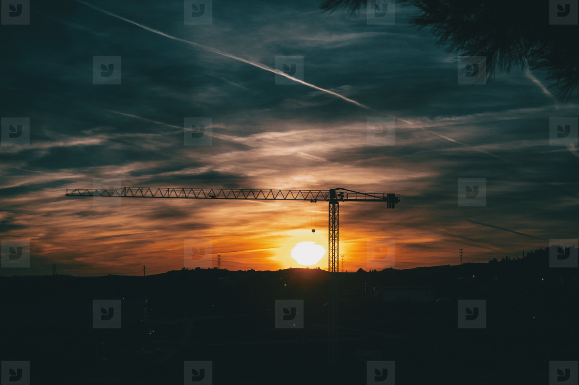Sunset with blue and orange clouds with the silhouette of a cons
