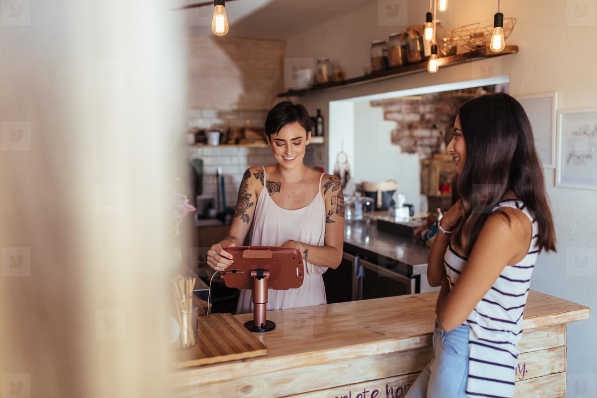 Woman entrepreneur taking orders at her restaurant