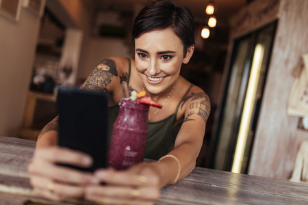 Woman taking a selfie for her food blog