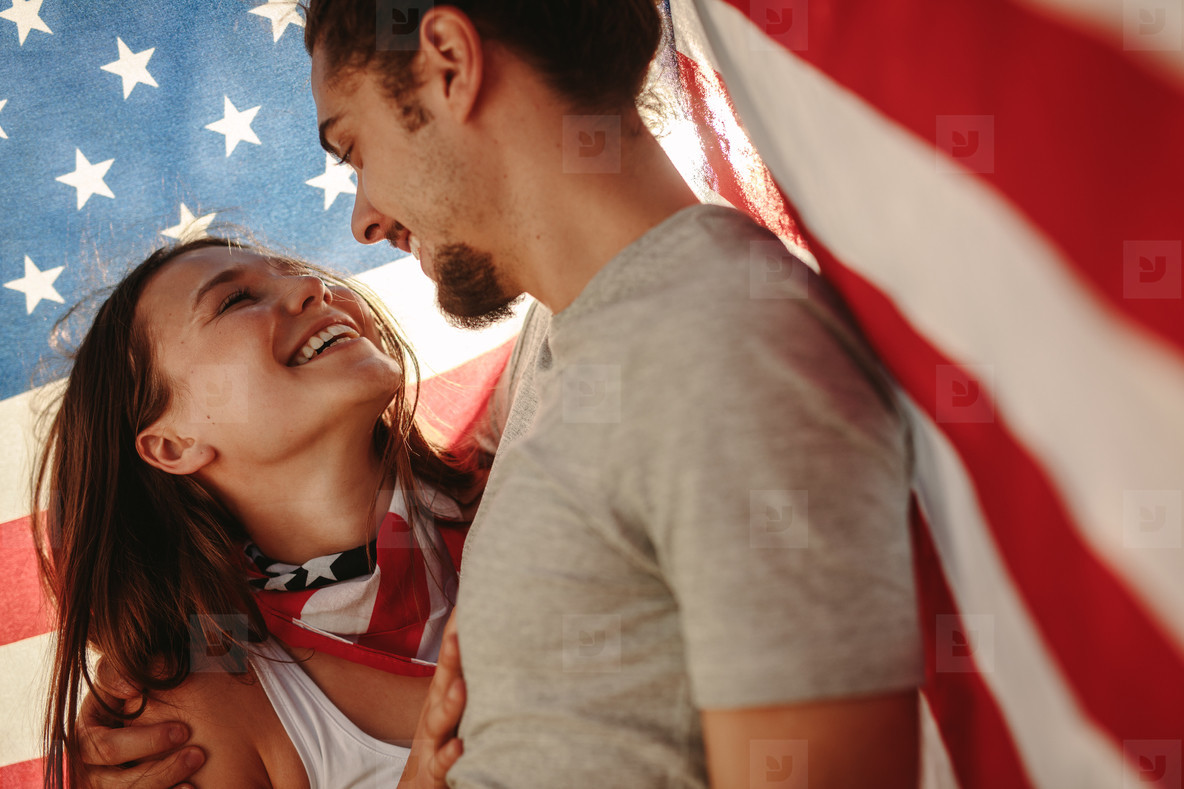 Affectionate couple under American flag