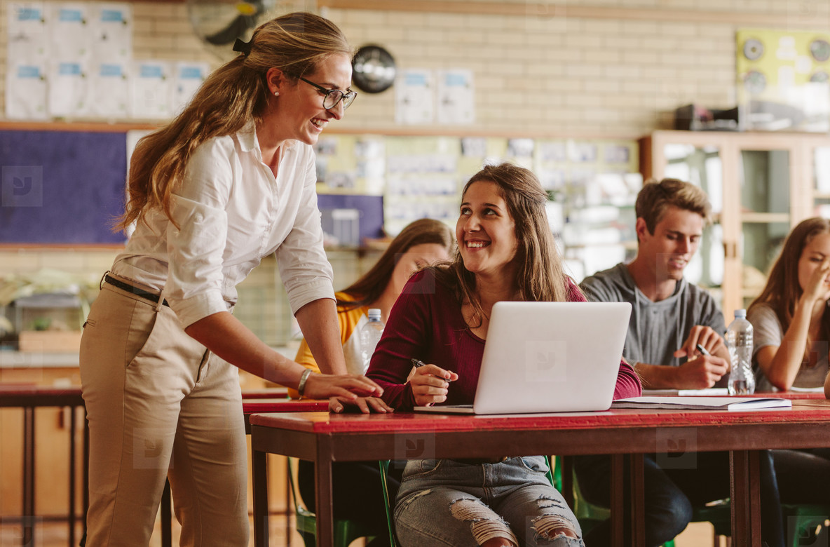 Woman high school professor helping student in class