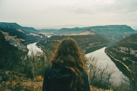 Girl from behind looking at the two roads of the meander of a ri