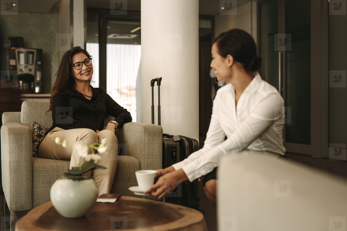 Businesswoman at airport lounge with waitress serving coffee