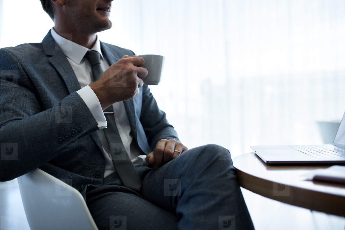 Businessman having coffee in office lobby