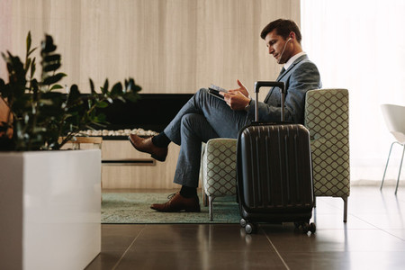 Businessman reading magazine in airport waiting room