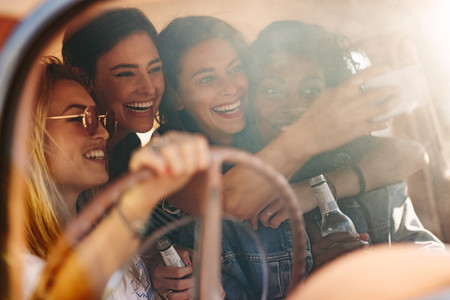 Young friends taking selfie in the car