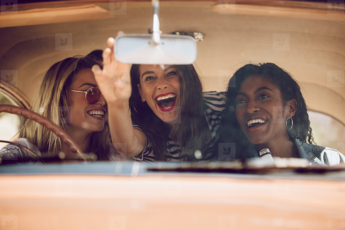 Cheerful female friends going on a road trip