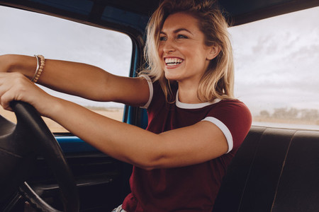 Smiling woman enjoying driving a car on road trip