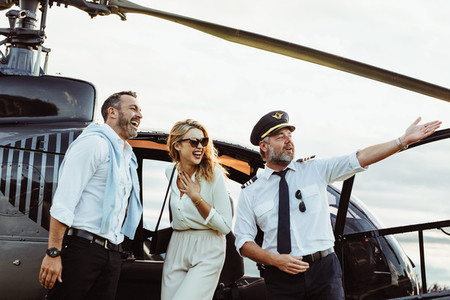 Smiling couple by a private helicopter with pilot