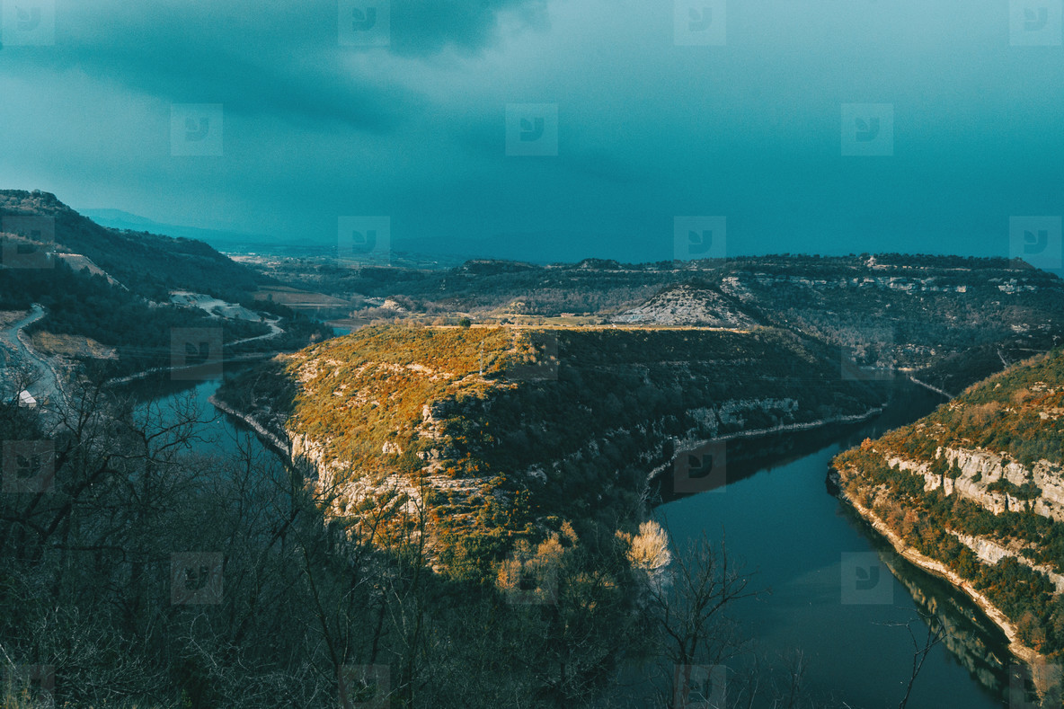 Landscape of a meander of a river at sunset on a cloudy day