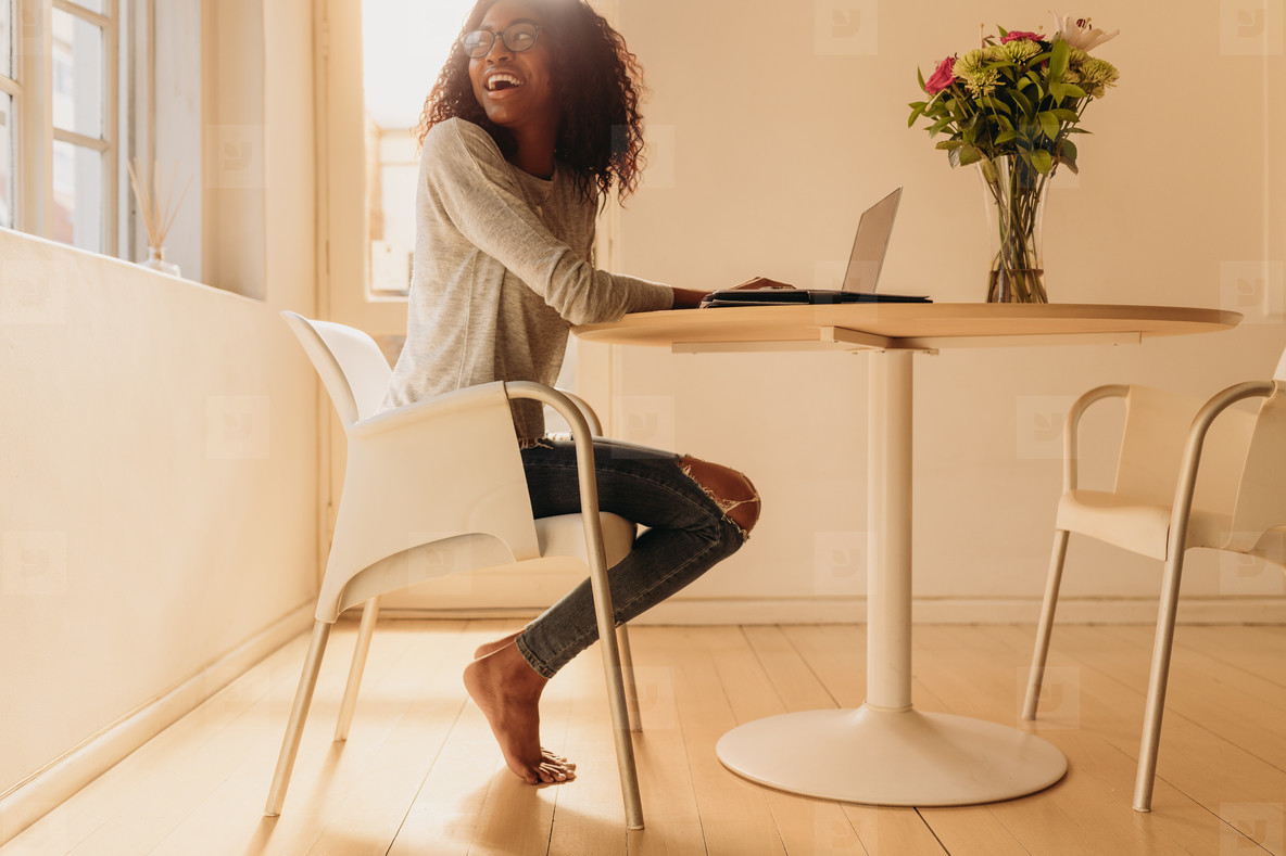 Woman managing business from home with mobile phone and laptop