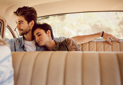 Couple traveling by an old car
