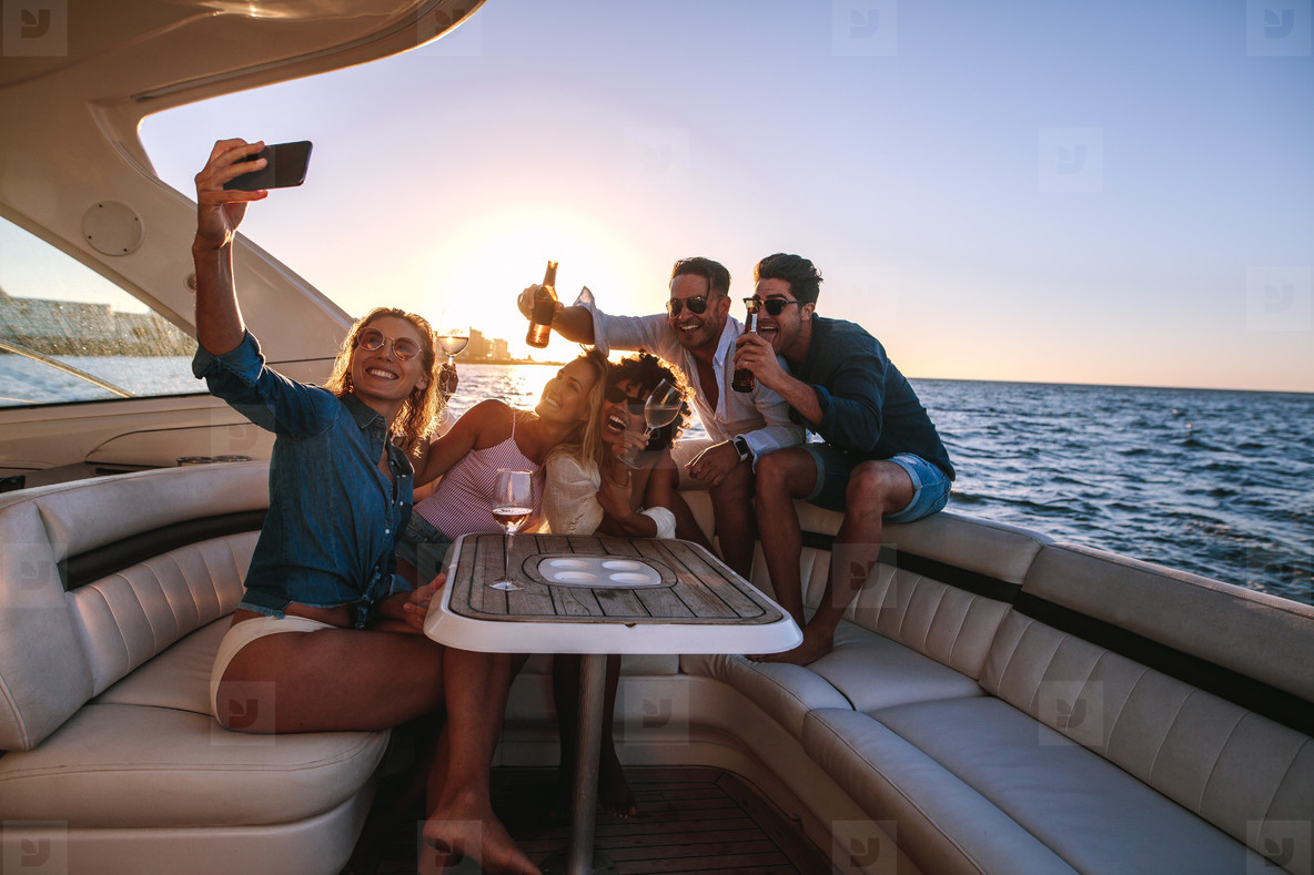 Group of people taking selfie at boat party