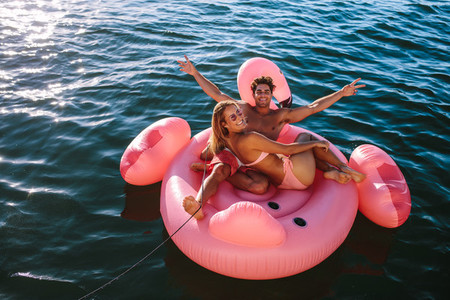 Couple enjoying inflatable toy ride behind a boat