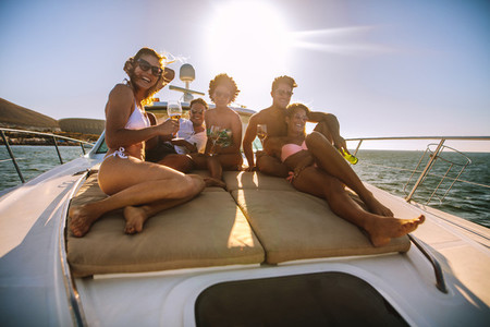 Group of friends sitting on the yacht deck with drinks
