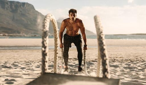 Man doing workout using battling ropes