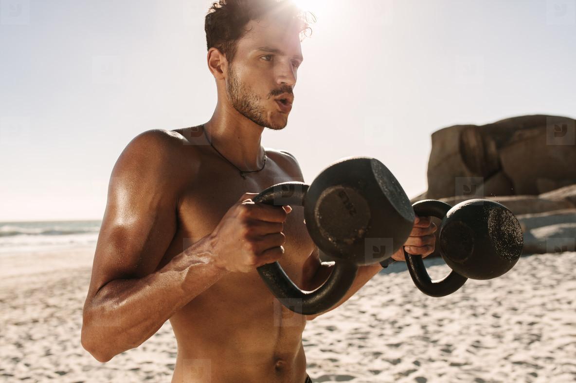 Man doing fitness training at the beach using kettlebells