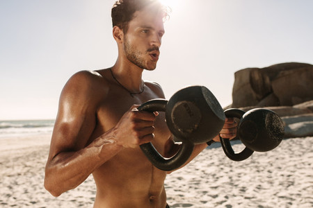 Man doing fitness training at the beach using kettlebells