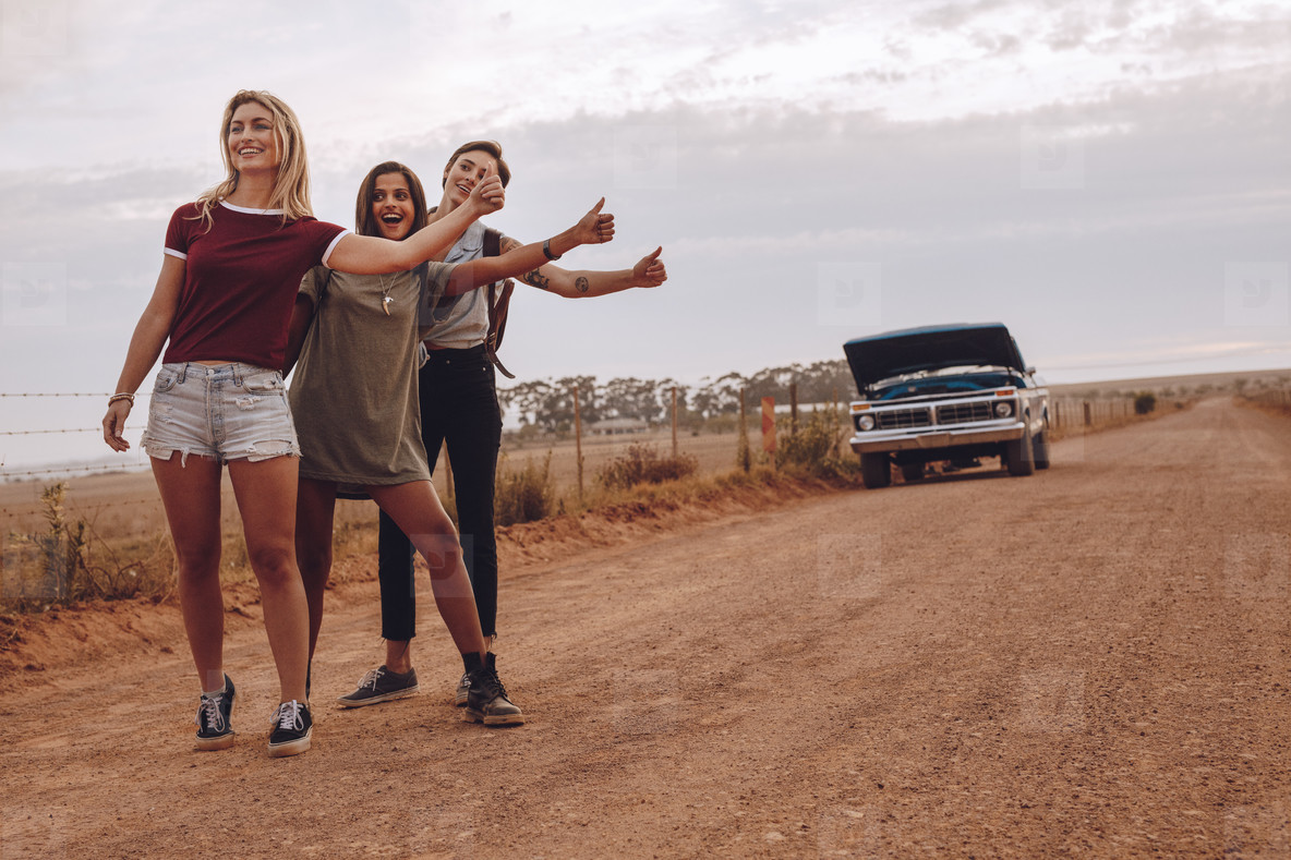Women hitchhiking near their broken car on country road