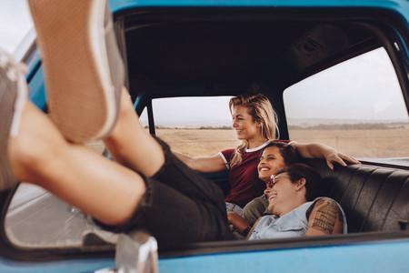 Female friends enjoying traveling by a car