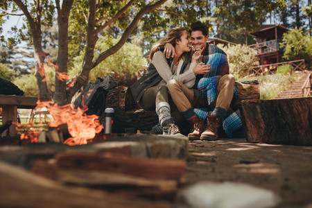 Loving couple relaxing near campfire