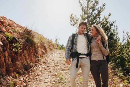 Couple walking down the mountain trail
