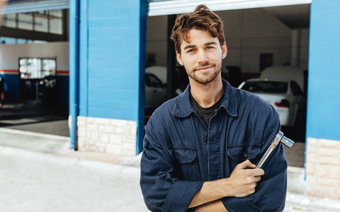Confident young car mechanic