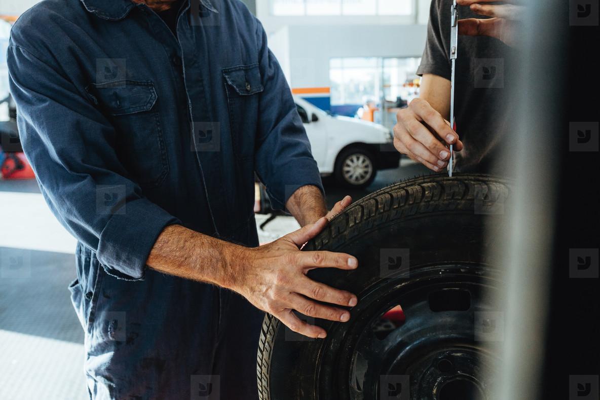 Technicians measuring the depth of tire tread instrument