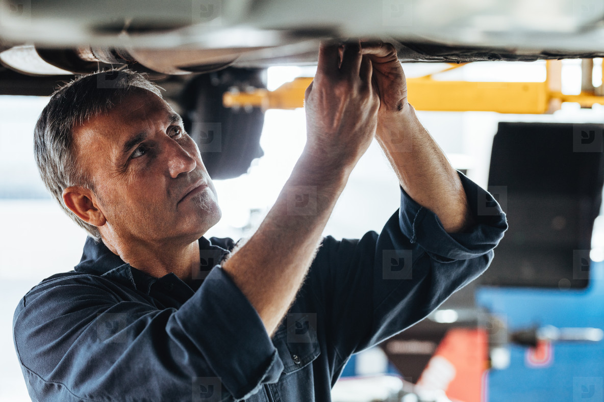 Auto mechanic fixing a car in service station