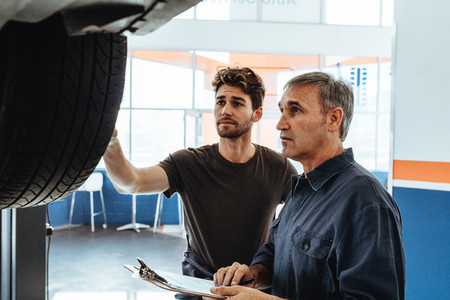 Mechanics examining the car and making notes in service station