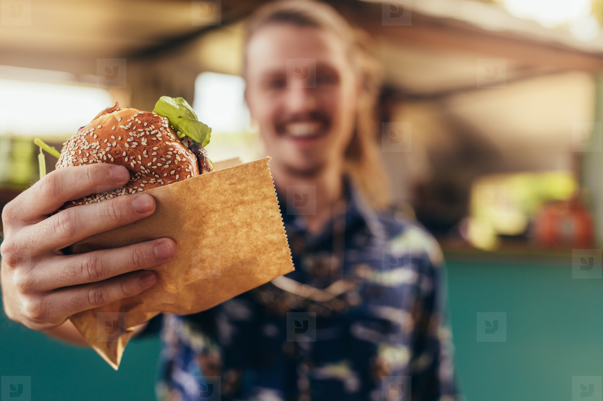 Man offering a food truck burger