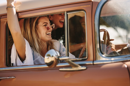Woman with friends enjoying a road trip drive