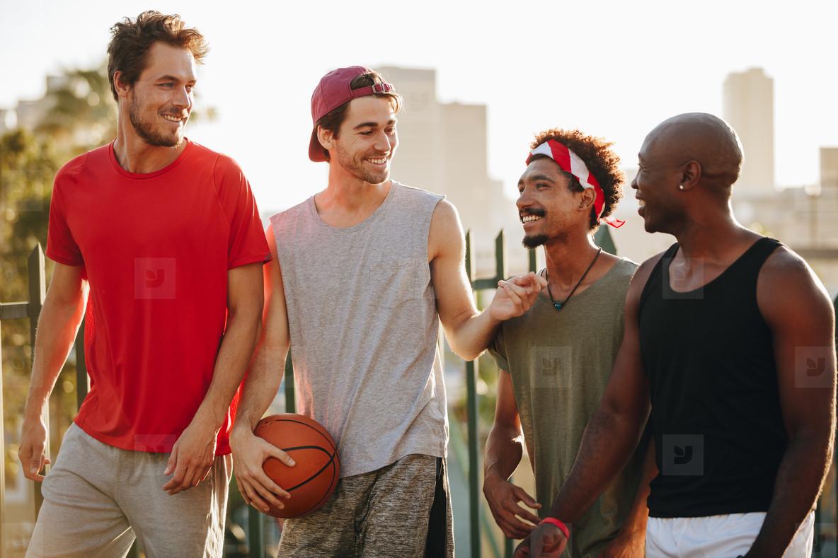Basketball guys walking on pavement with the ball