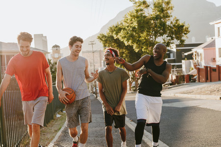 Basketball guys walking on pavement with the ball