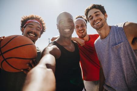 Men playing basketball posing for photo