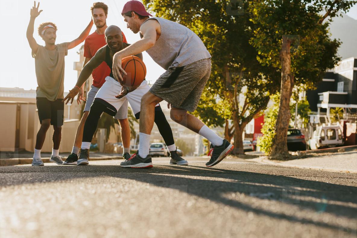 Men playing basketball on street