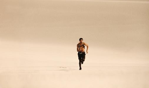Fitness man running n desert