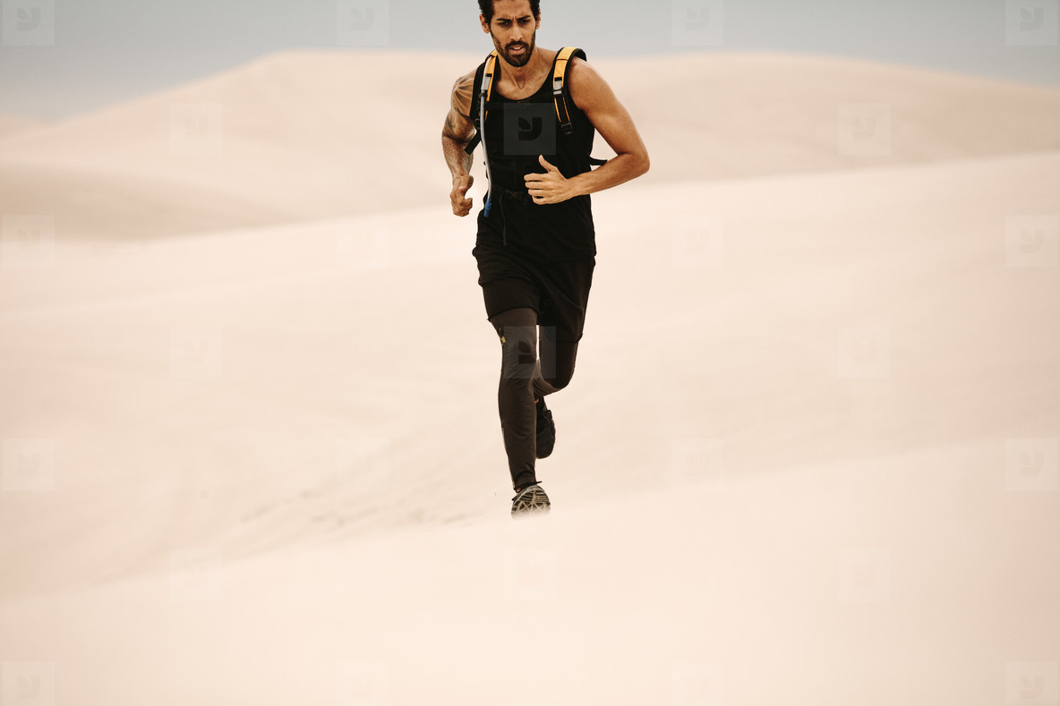 Man running on sand dunes